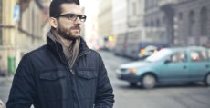 A young man with beard wearing glasses standing in the street