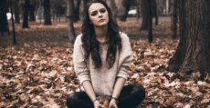 A woman feeling sad sitting in a park surrounding by autumn leaves